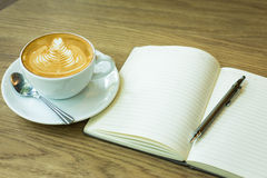 Hot latte art coffee cup on wooden table and note book, vintage Stock Photo
