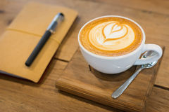Hot latte art coffee cup on wooden table and note book, vintage Royalty Free Stock Image