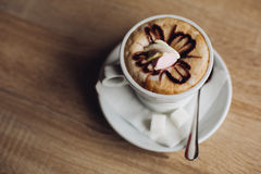 Hot latte art coffee decorated,  Hot mocha coffee decorated on wooden table. Stock Photos