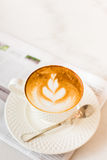 Hot latte art coffee with newspaper on wooden table, vintage and Royalty Free Stock Photo