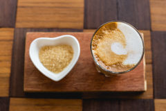 Hot latte art coffee with newspaper on wooden table, vintage and Stock Image