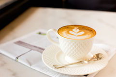 Hot latte art coffee with newspaper on wooden table, vintage and Stock Photos