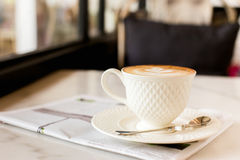 Hot latte art coffee with newspaper on wooden table, vintage and Stock Images