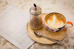 Hot latte art coffee with newspaper on wooden table, vintage and Royalty Free Stock Photos