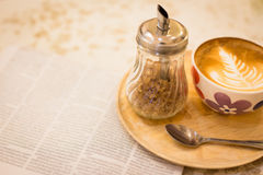 Hot latte art coffee with newspaper on wooden table, vintage and Royalty Free Stock Image