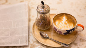 Hot latte art coffee with newspaper on wooden table, vintage and Royalty Free Stock Photography