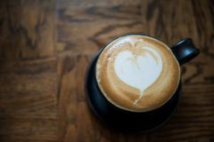 Hot Latte art Coffee on wooden table. Hot Latte art Coffee in a cup on wooden table by top view with copy space for text. Heart shape milk foam made by Stock Image