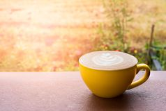 Hot latte coffee. In a beautiful yellow cup in the early morning garden stock images