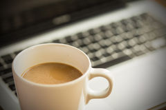 Hot latte coffee cup and laptop on wood background and texture. Stock Image