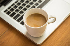 Hot latte coffee cup and laptop on wood background and texture. Royalty Free Stock Images