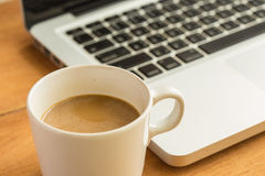 Hot latte coffee cup and laptop on wood background and texture. Royalty Free Stock Image