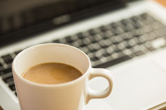 Hot latte coffee cup and laptop on wood background and texture. Royalty Free Stock Photos