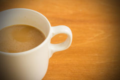 Hot latte coffee cup on wood background and texture. Royalty Free Stock Images