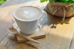 Hot latte coffee in glass cup mug on wood table. Hot latte coffee in glass cup mug on wooden table stock photo