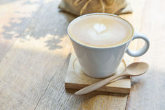 Hot latte coffee in glass cup mug. On wooden table royalty free stock photography