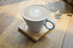 Hot latte coffee in glass cup mug. On wooden table royalty free stock image