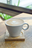 Hot latte coffee in glass cup mug. On wooden table stock photography