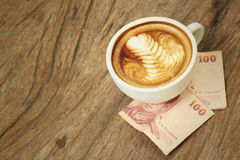 Hot latte coffee with money of Thai Bath Stock Photography
