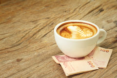 Hot latte coffee with money of Thai Bath Royalty Free Stock Images