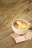 Hot latte coffee with money of Thai Bath Stock Images