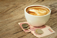 Hot latte coffee with money of Thai Bath Royalty Free Stock Image