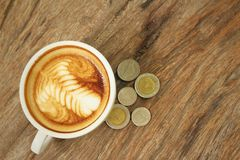 Hot latte coffee with money of Thai Bath Royalty Free Stock Photography
