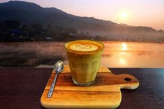 Hot latte coffee is placed on a wooden tray. royalty free stock image
