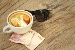 Hot latte , sunglasses with money of Thai Bath. Royalty Free Stock Images