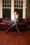 Hot Leather. Model wearing leather boots on a leather sofa Royalty Free Stock Photos