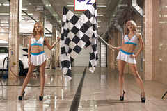 Hot leggy models with race flags at car wash. Full length shot of two hot leggy models at car wash service posing to camera with checkered race flag Royalty Free Stock Images
