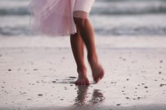 Hot Legs. Action and motion shot of legs walking on the beach at sunset in pink dress stock image