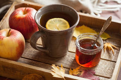 Hot lemon honey tea warming drink scarf cozy autumn leaves royalty free stock photography