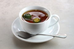 Hot Lemon Tea. With two green lime in the cup Stock Image