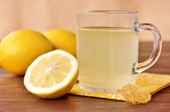 Hot lemon tea with fresh lemons. A glass hot lemon tea on a wooden table with fresh lemons Stock Image