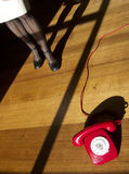 Hot line. Woman approaches hotline retro red phone in dramatically lit scene Stock Photography