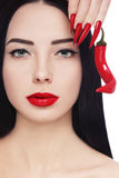 Hot lips. Portrait of young beautiful brunette with red lipstick, long stiletto nails and hot chili pepper in her hand over white background stock photography