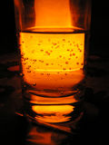 Hot liquid 1. Glass with mineral water illuminated from behind by candlelight Stock Image
