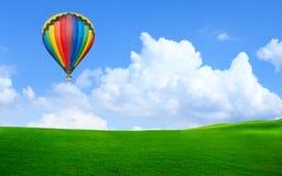 Hot luftar ballongen som svävar i skyen över land Royaltyfri Fotografi