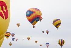 Hot luftar ballonger i flyg Arkivbilder