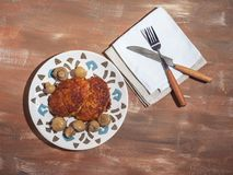 Hot lunch of turkey and pickled mushroom cutlets on a decorative plate, cutlery. Hot lunch of turkey and marinated mushrooms cutlets on a decorative plate stock image