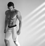 Hot male fitness model. Sexy black and white portrait of young muscular male fitness model in underwear with window light streaming in Stock Image
