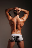 Hot male model. Young muscled male model posing in studio Stock Image