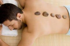 hot male relaxing stone treatment Στοκ Φωτογραφία