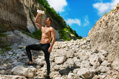 Hot Man Pouring Refreshing Water Over Face After Exercising Outdoors Stock Photo