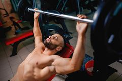 A hot man with strong muscular body performs a bench press using a barbell on a blurred dark background. A sexy man with naked strong torso lifting a barbell on Stock Images