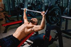 A hot man with strong muscular body performs a bench press using a barbell on a blurred dark background. A sexy man with naked strong torso lifting a barbell on Royalty Free Stock Image