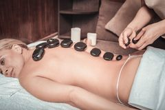 Hot black stones lying in the row. Hot massage. Hot black stones lying on the female back in the row royalty free stock photos