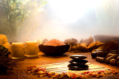 Hot Massage Polished Stones in a Relaxation Spa. Black hot massage polished stones cairn with body care treatment products and calm relaxing mood natural Royalty Free Stock Image