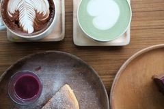 Hot matcha green tea with heart latte art. cheese cake with berry syrup on wood tray. Hot matcha green tea with heart latte art. cheese cake with berry sauce on stock photography