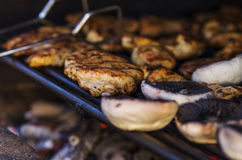 Meat and mushrooms on grill. Mushrooms and roasted  meat on a hot grill Stock Images